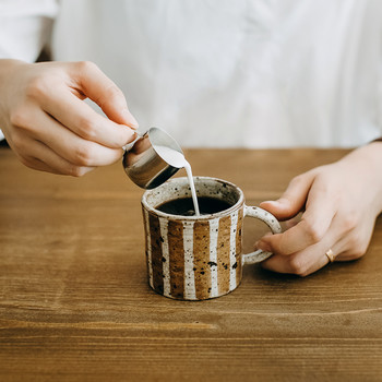 Person pouring milk into cup of coffee