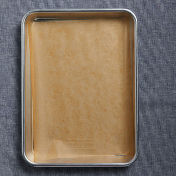 empty baking sheet with waxed paper on grey background