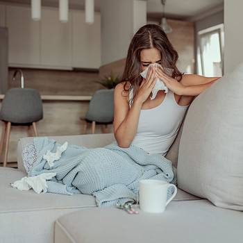 Sick woman sitting on couch with the flu