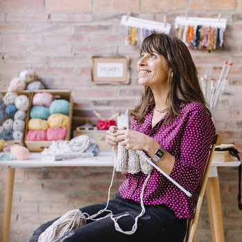 smiling woman who is knitting