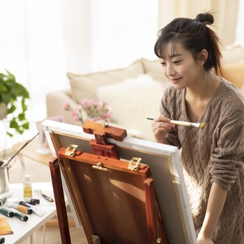 young woman painting at home