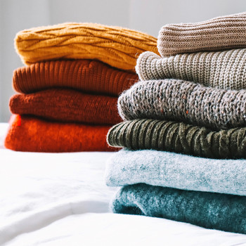 folded sweaters on bed