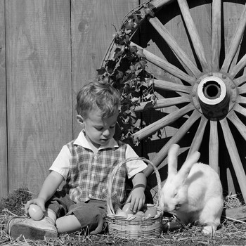 little boy and bunny sitting by tractor wheel