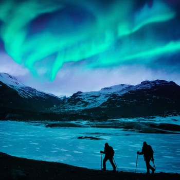 two hikers under the northern lights