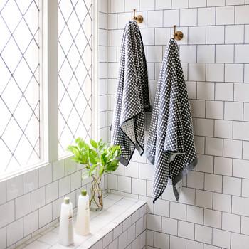 bronze hooks in white tile shower