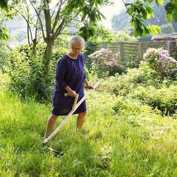 woman scything grass in yard