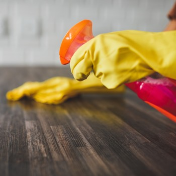 woman cleaning kitchen countertop with gloves on