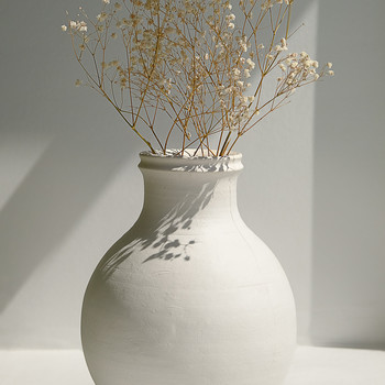 babys breath arranged in a white clay vase