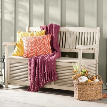 storage bench with pillows and knit blanket