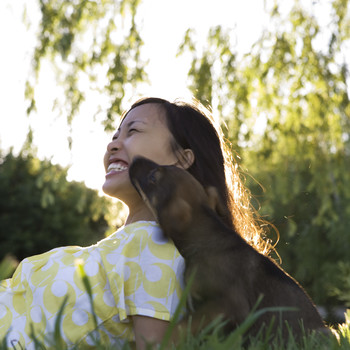 woman and dog bonding outside in grass