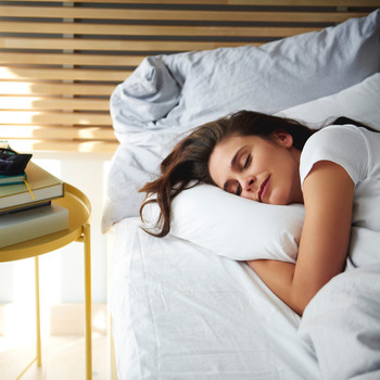 Woman sleeping in bed near sunlight