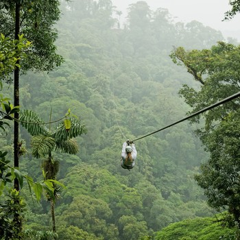 Woman ziplining in Costa Rica over rainforest