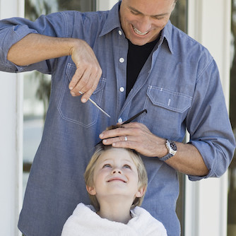 father cutting son's hair