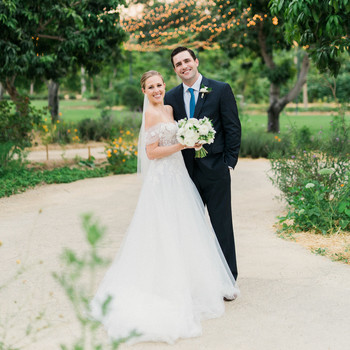 wedding couple posing on sandy path with string lights behind