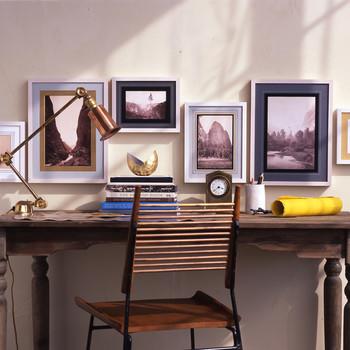 framed landscape photography hanging above writing desk