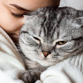 woman snuggling her pet cat
