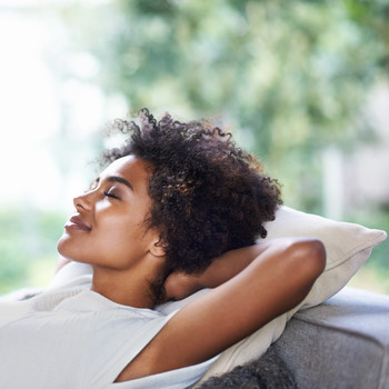 Shot of young woman resting at home on couch