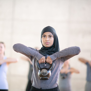 woman exercising with kettle ball