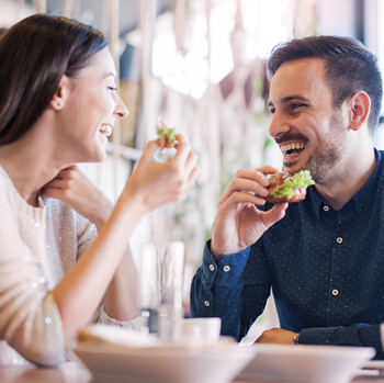 young couple eating together in cafe