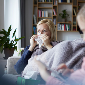 Woman sitting in living room blowing nose
