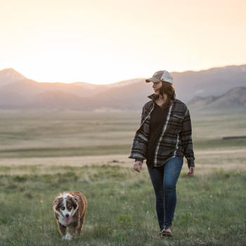 Woman Walking Dog in a Field