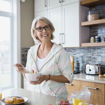 Woman Eating Salad While Standing in Kitchen