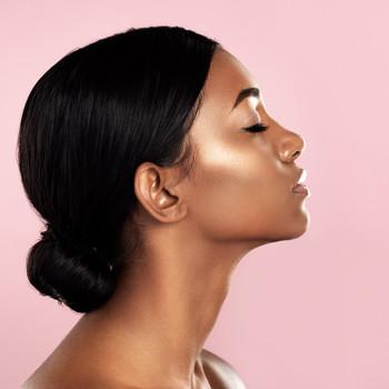 woman with hair in low bun skin glowing