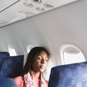 woman sleeping at window seat on airplane