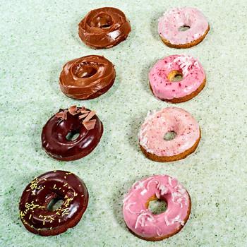 rows of doughnuts on green countertop