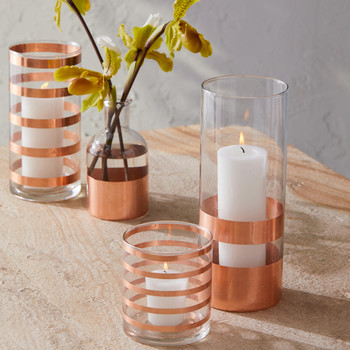 copper striped glassware containing candles