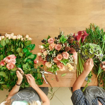 two florists making bouquets in flower shop