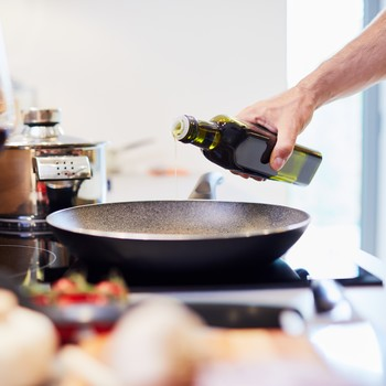 Man Pouring Oil Into a Pan to Cook