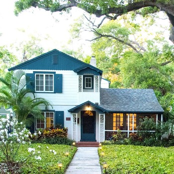 white and blue house with palms and groundcover in yard