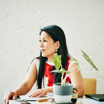 woman sitting at work desk with plant