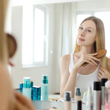 woman looking in mirror brushing hair