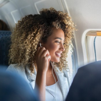 women on airplane flight looking out window