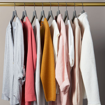 shirts and sweaters hanging from clothing rack
