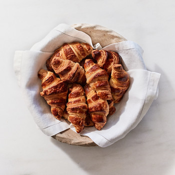 pile of croissants in a linen draped bowl