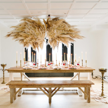 romeo and juliet valentines day party table setting with pampas grass angel wings hanging above