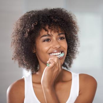 woman looking in mirror brushing teeth