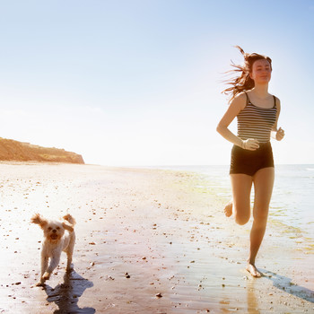 woman and dog running on beach