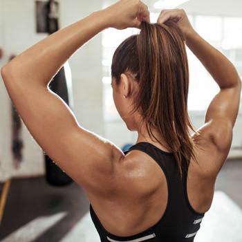 woman adjusting ponytail at the gym