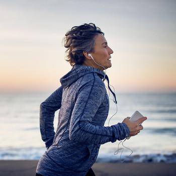 Woman running along shoreline