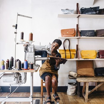 woman sewing leather goods at her store