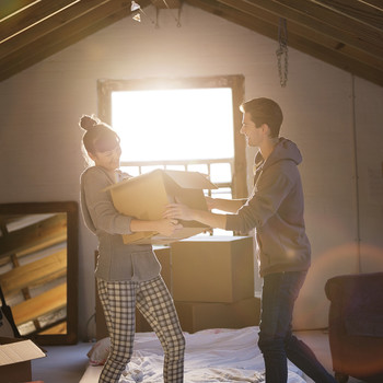 couple with box in attic