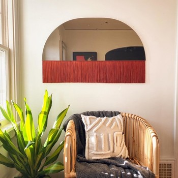 red fringe-lined mirror with a boho aesthetic hanging on a wall