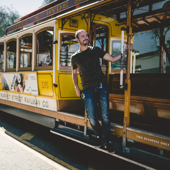 Man Standing on a Cable Car