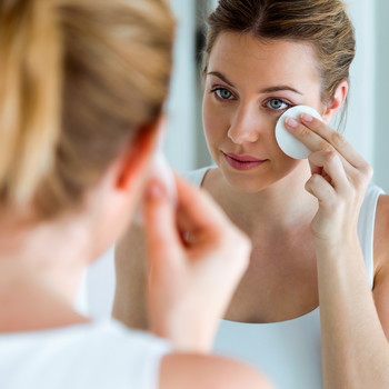 woman removing makeup in mirror