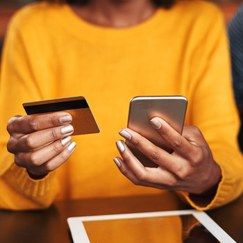 woman in a cafe shopping online with credit card
