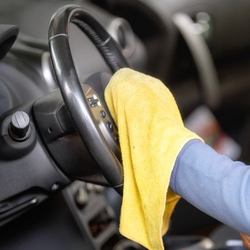 person cleaning car steering wheel